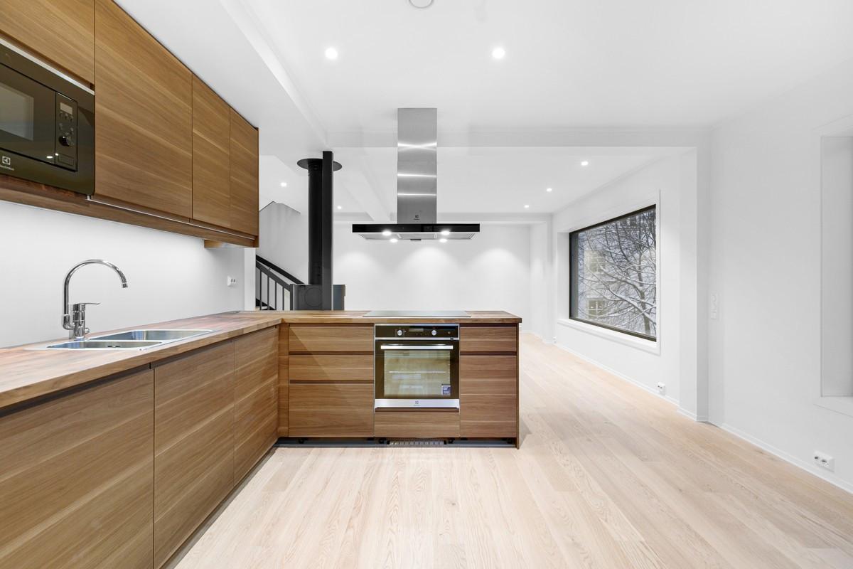 Kjøkken holder høy standard med integrerte hvitevarer og halvøy som åpner opp mot stue