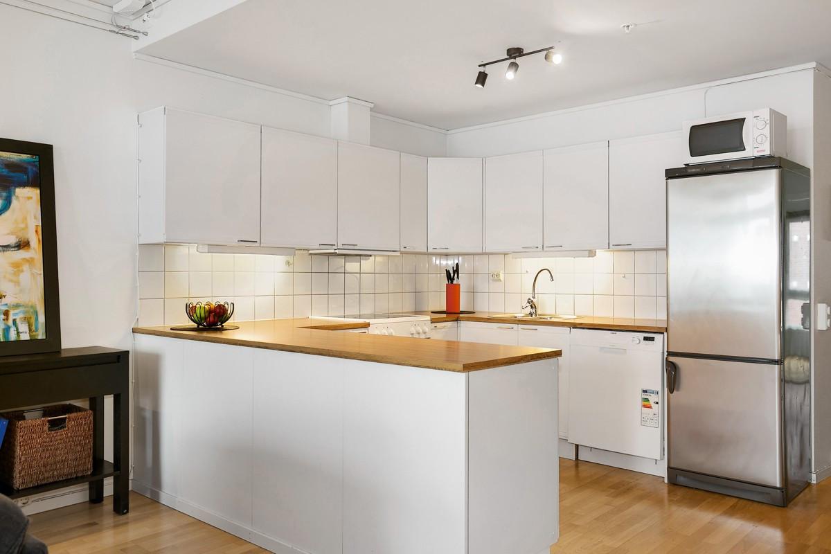Lyst og trivelig kjøkken med god skapplass og barløsning mot stue