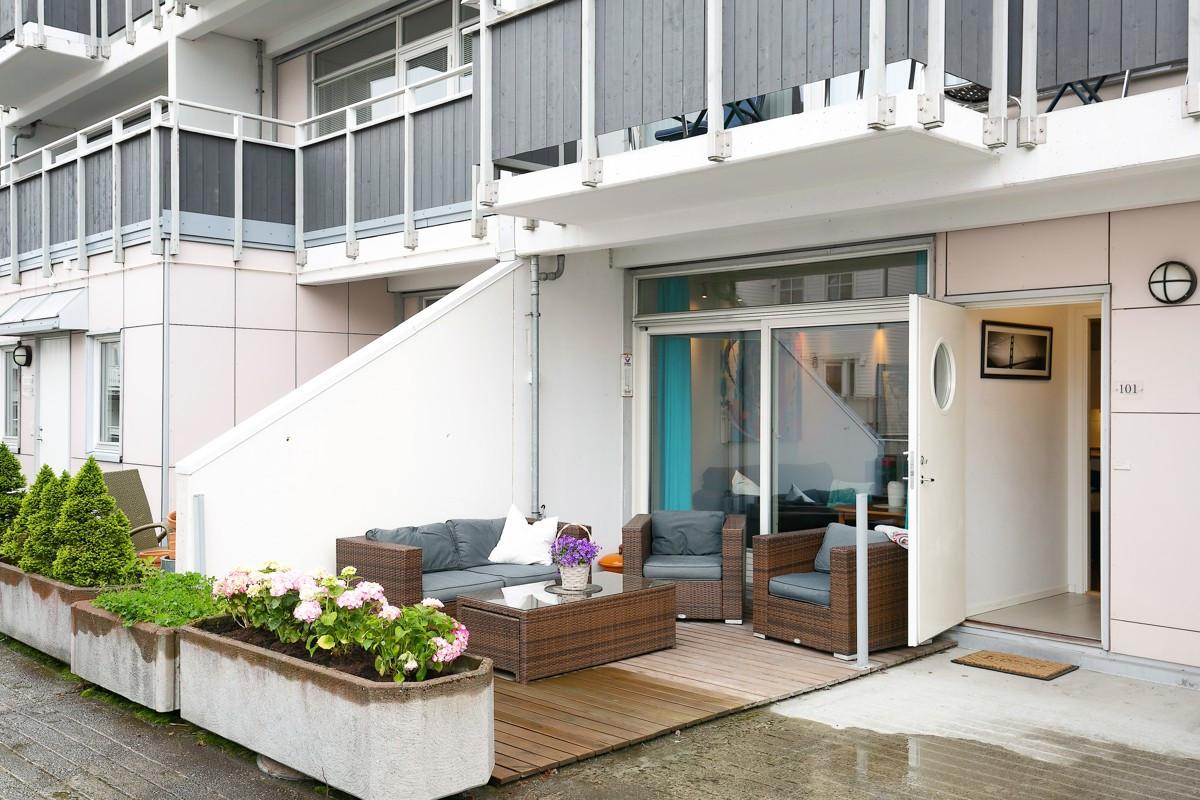 Inngangsparti på bakkeplan med romslig terrasse
