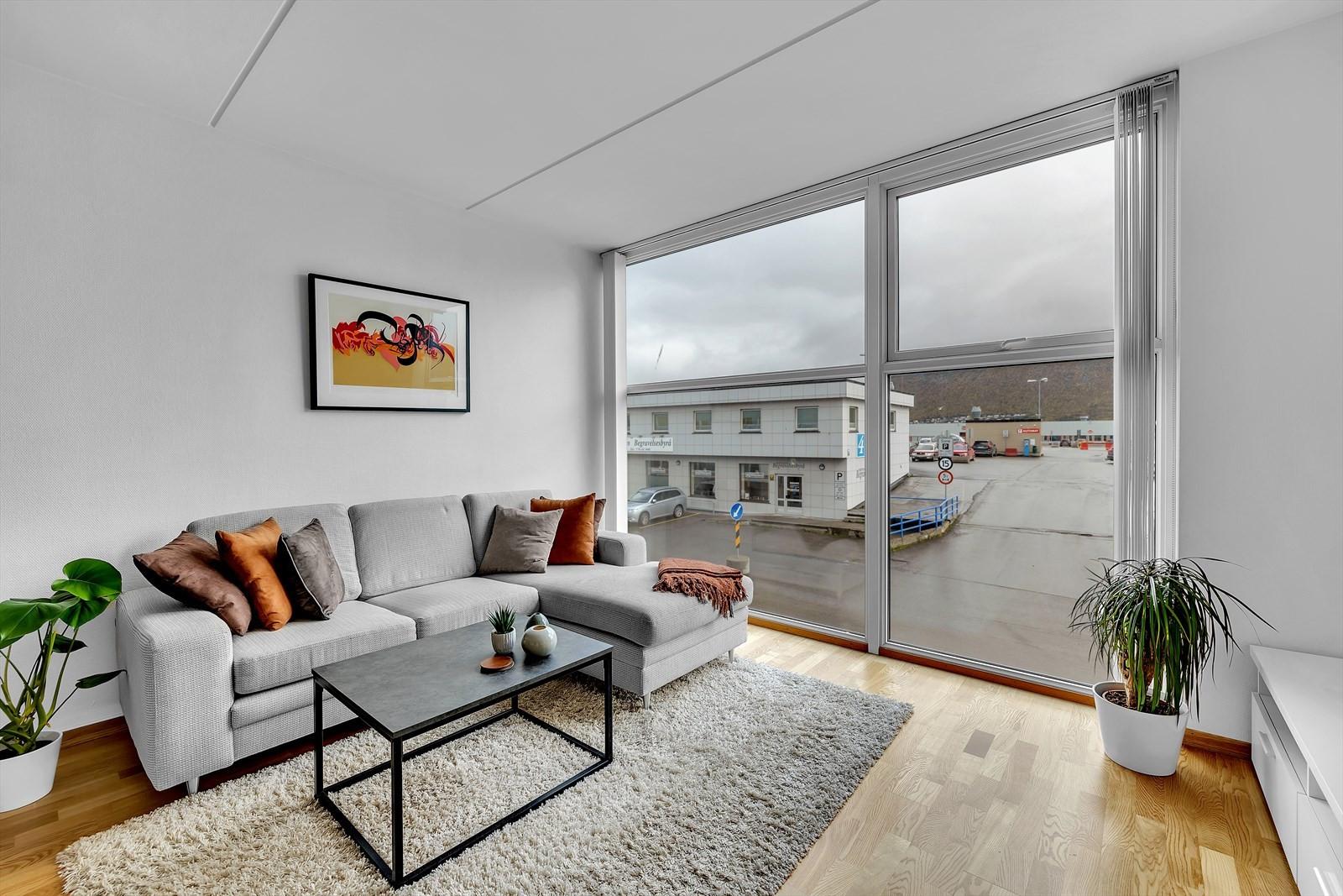 Lys og trivelig stue med store vindusflater og god takhøyde.