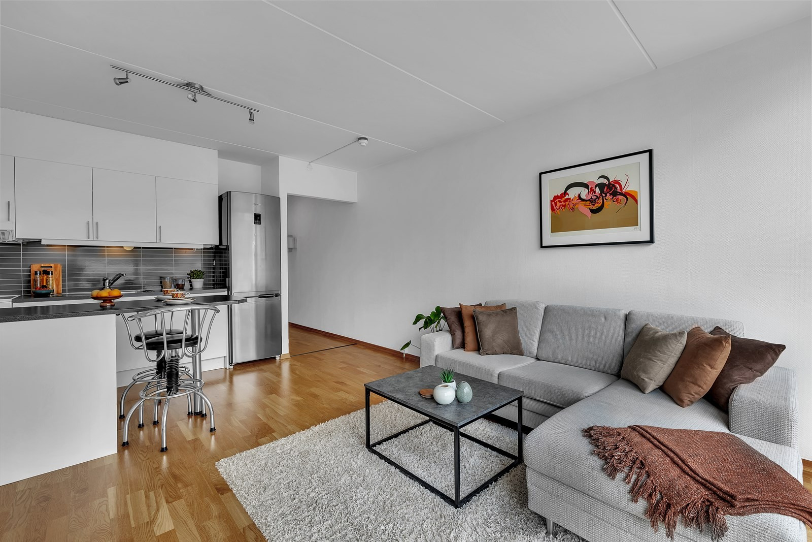 Stuen har åpen løsning med kjøkken. Praktisk benk mot stuen.