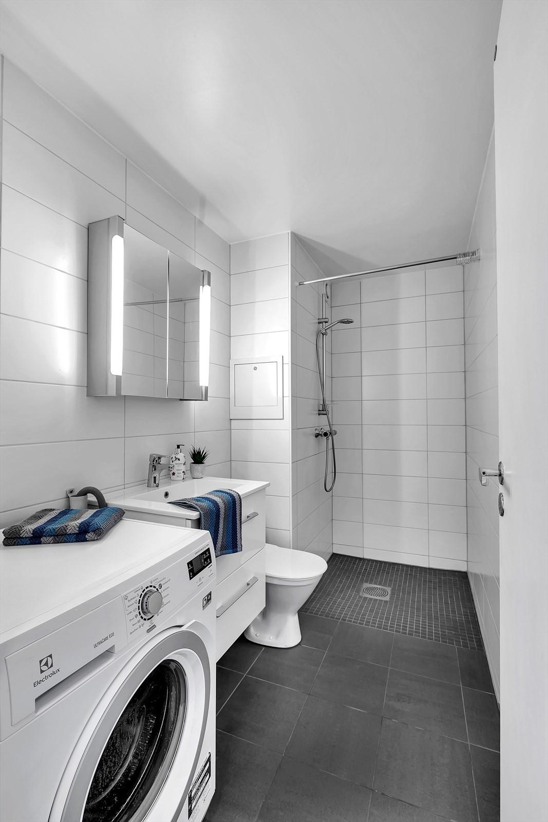 Flislagt badrom med moderne uttrykk og nøytrale farver.