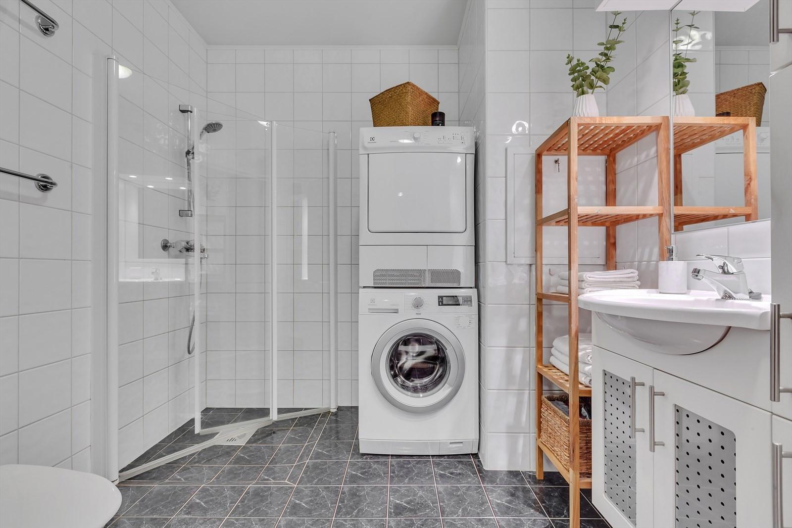 Flislagt bad med dusjhjørne, wc, opplegg til vaskemaskin/tørketrommel og servant med under og sideskap.