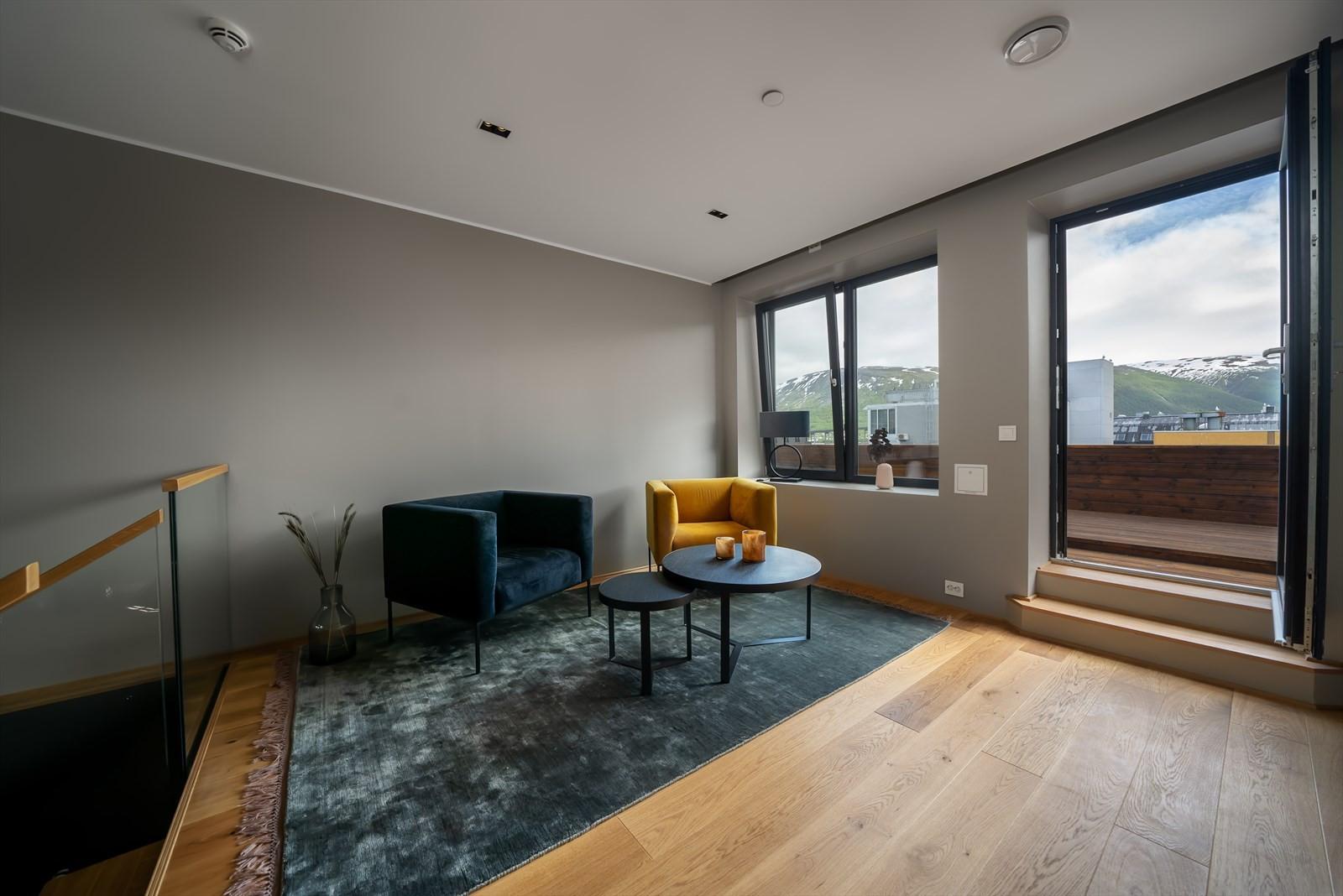 I leilighetens 2. etasje finner du denne koselige stuen og stor veranda