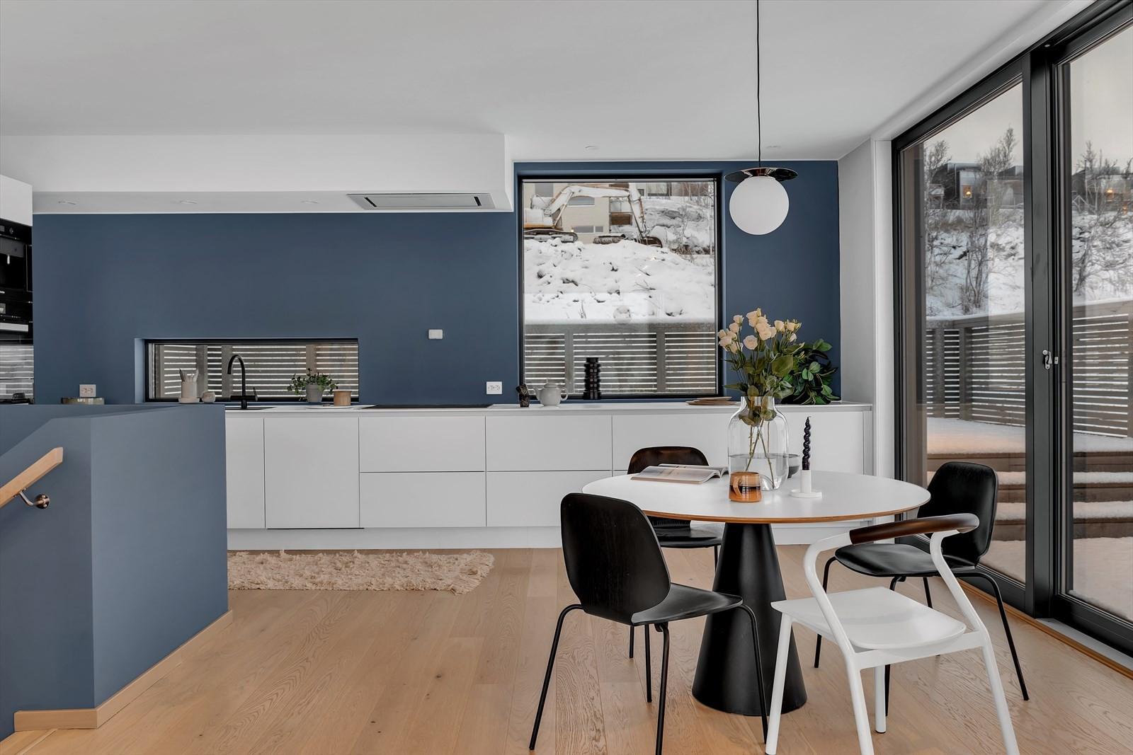 Innholdsrikt kjøkken med store vinduer/utgang til terrasse.