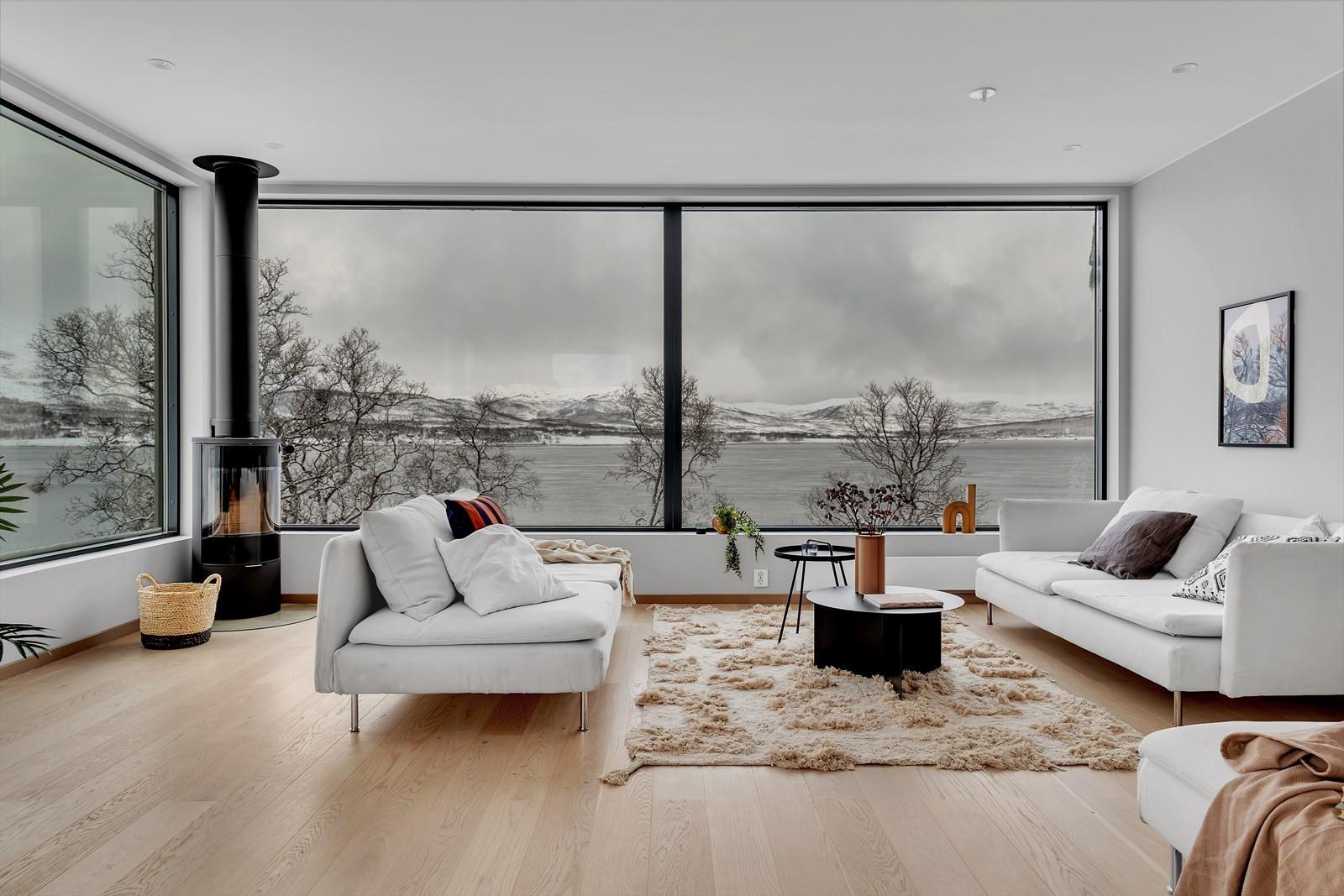 Stue med panoramavinduer mot sjøen.