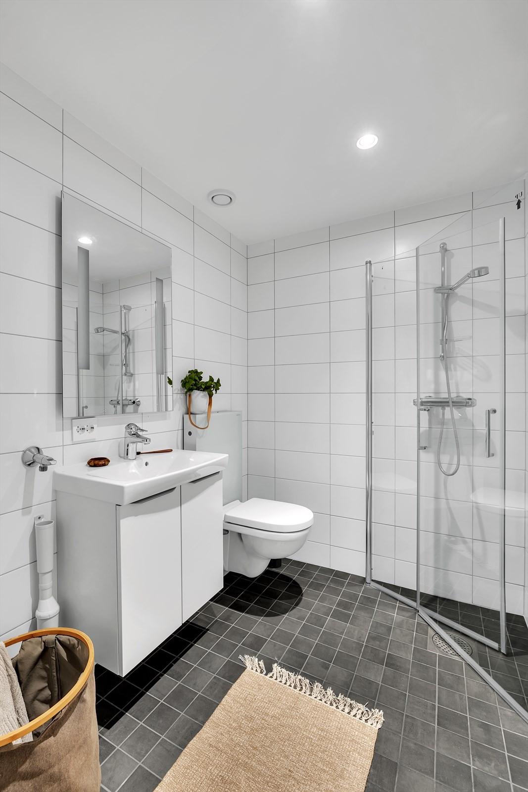 Flislagt bad med vegghengt wc, dusj og uttak for vaskemaskin i kjelleren
