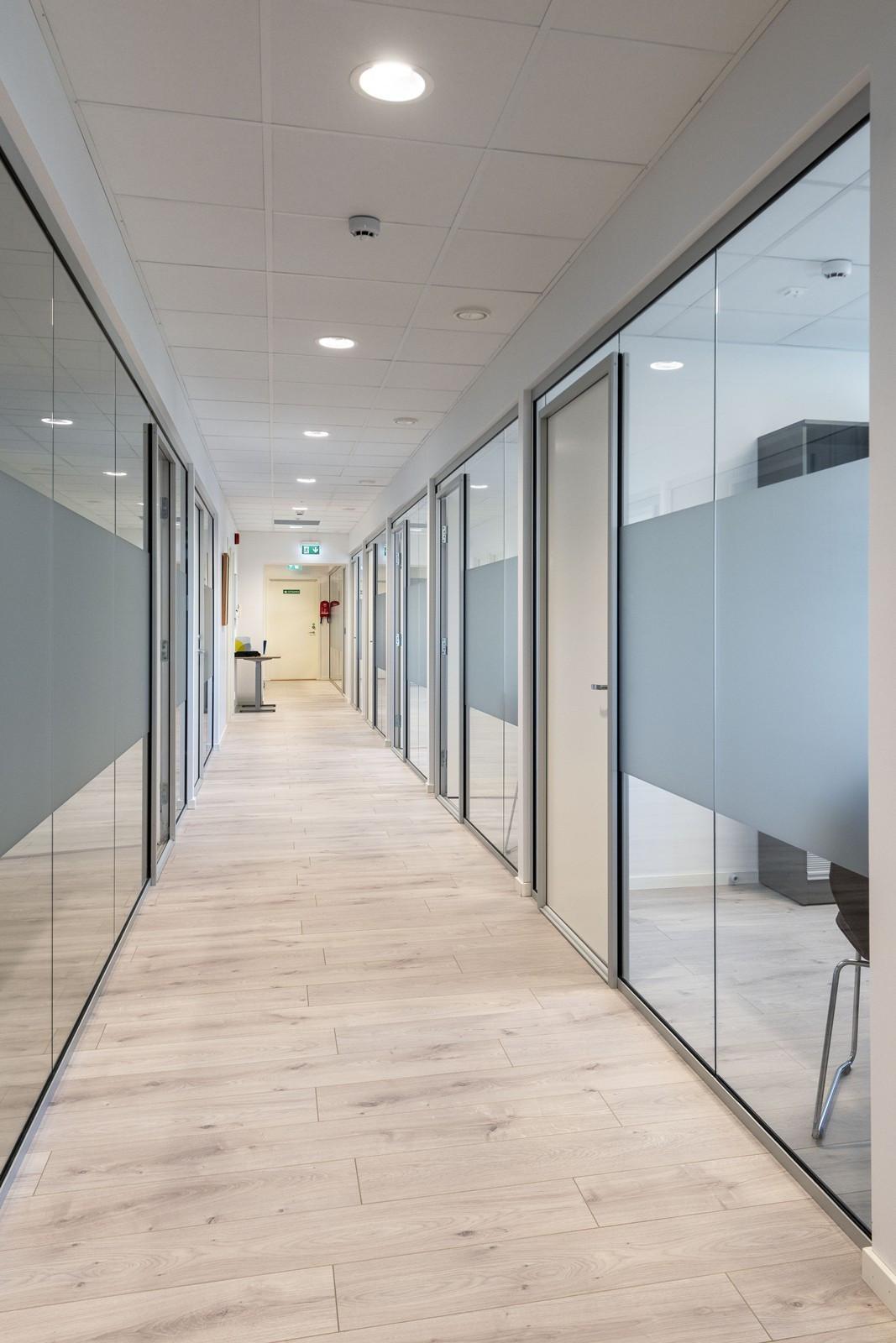 Lyse gangarealer med glass mellom cellekontor og fellesarealer