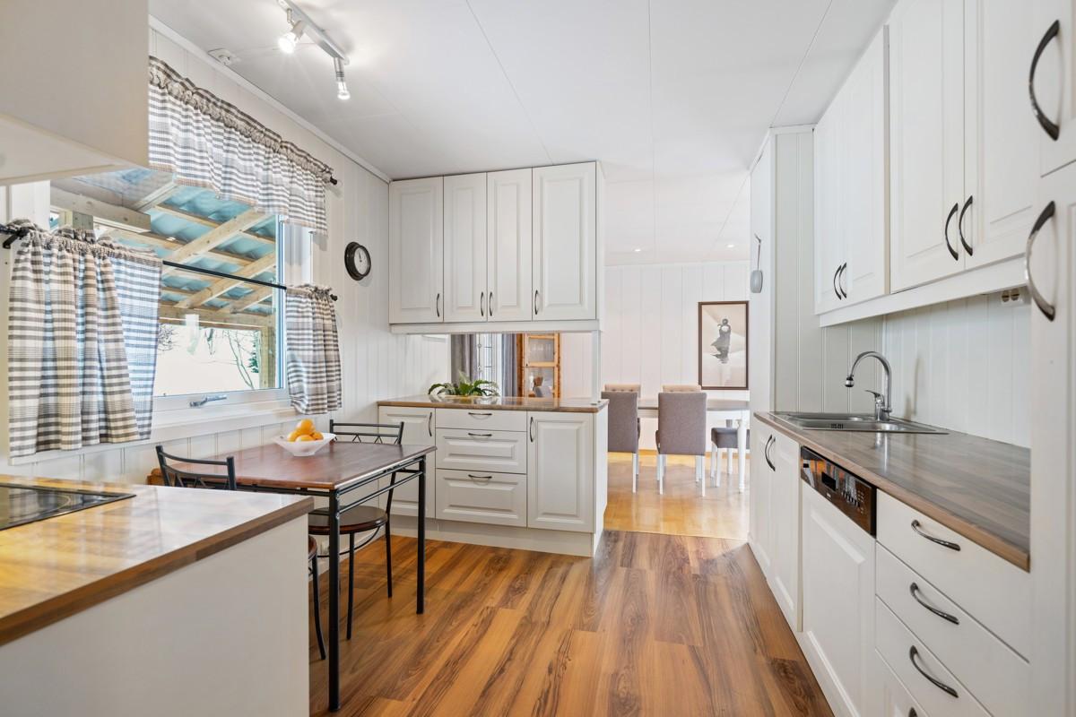 Kjøkken har rikelig med skapplass, vindu for lys og plass for kjøkkenbord
