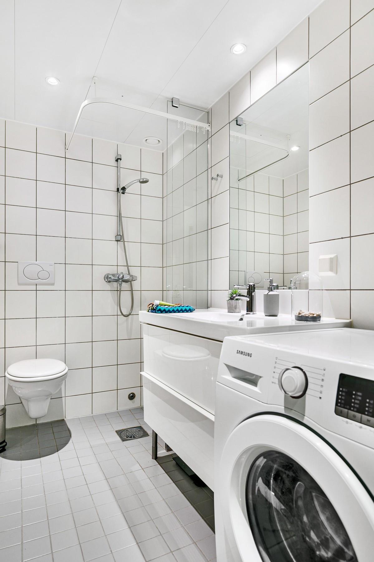 Komplett flislagt baderom med stor dusjnisje og opplegg for vasdkemaskin