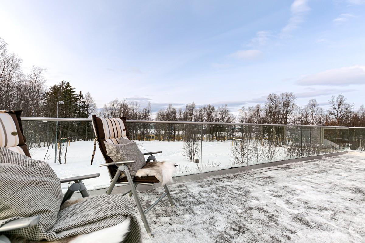 Stor terrasse på rundt 29 kvm og glassrekkverk som gir luft