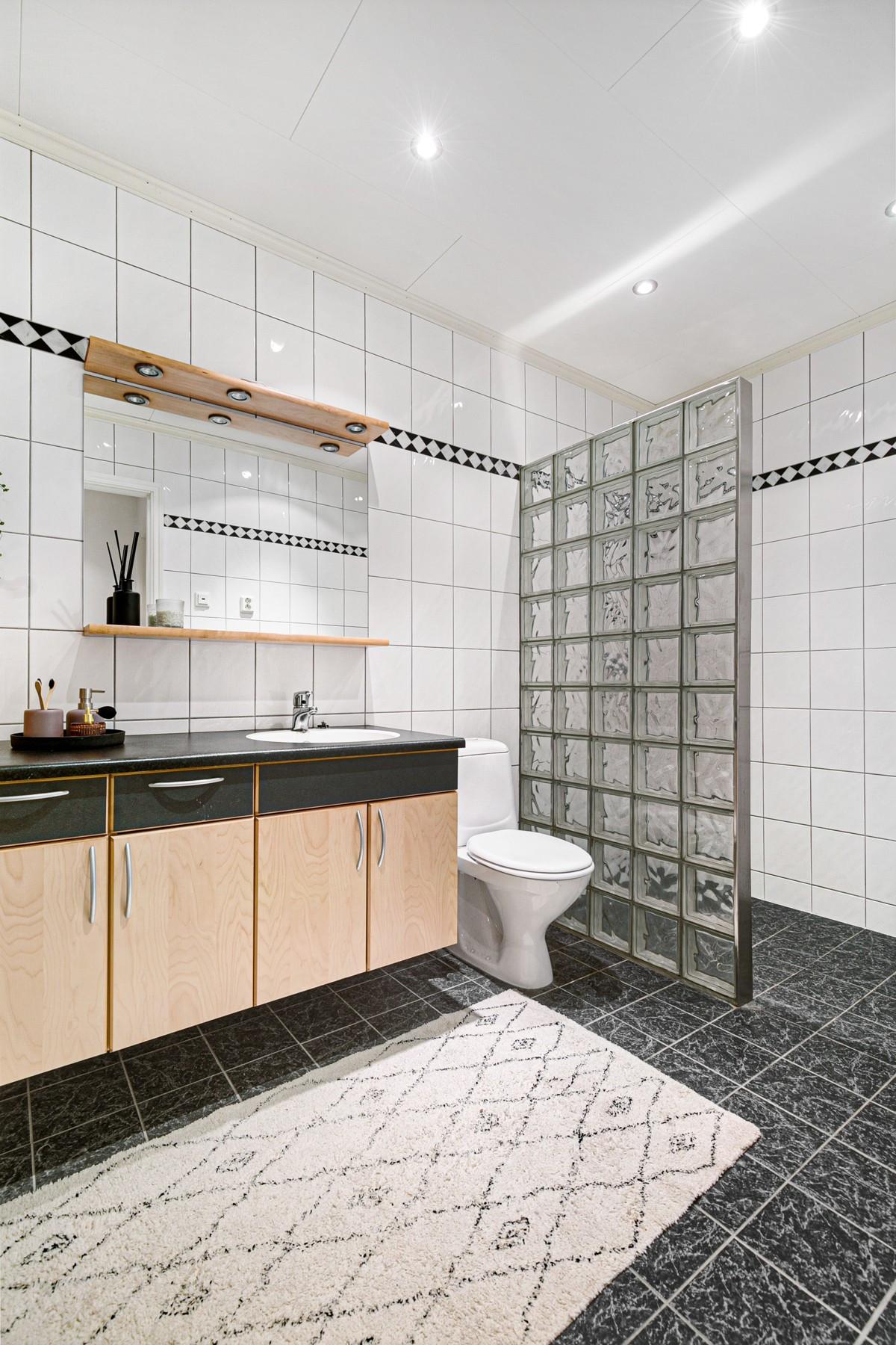 Fliselagt og stort baderom med dusjnisje