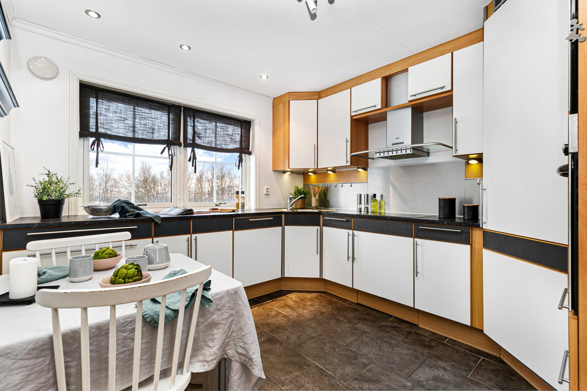 Kjøkken med rikelig med skapplass, vindu og rom for eget frokostbord