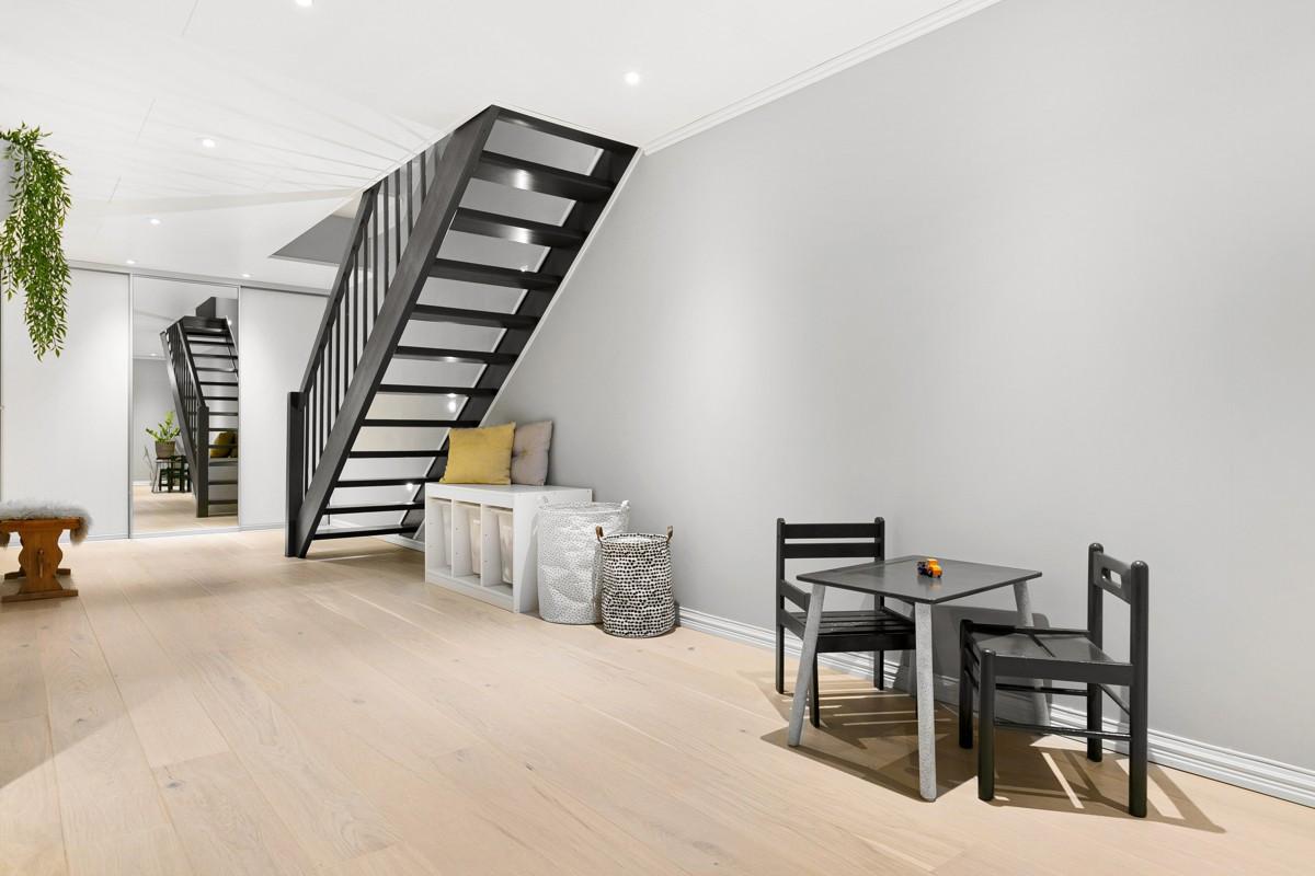 Trapp og gang i kjeller holder en moderne standard med stor skyvedørsgarderobe