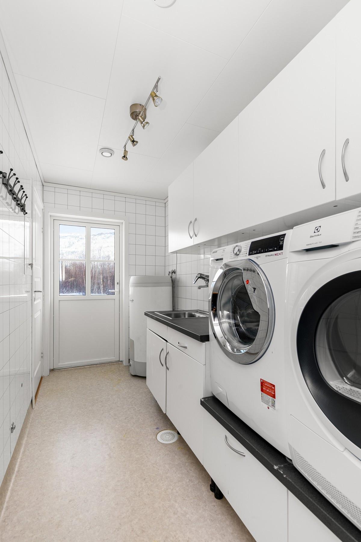 Praktisk vaskerom med egen inngang. Stor innredning med plass til vaskemasking og tørketrommel