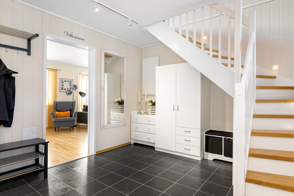 Stor og romslig entré. Moderne trapp med belysning som tar deg mellom etasjene.