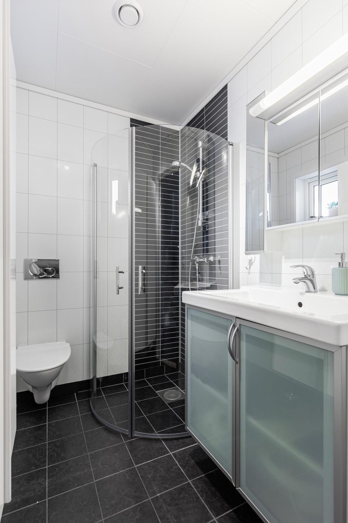 Baderom i 1. etasje med vegghengt toalett, dusjnisje, samt baderomsinnredning