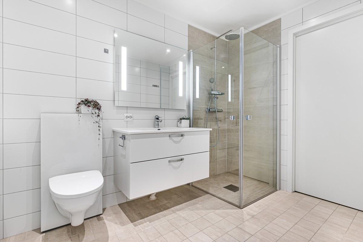 Komplett fliselagt baderom med dusjhjørne, baderomsinnredning med servant og speil, samt vegghengt toalett
