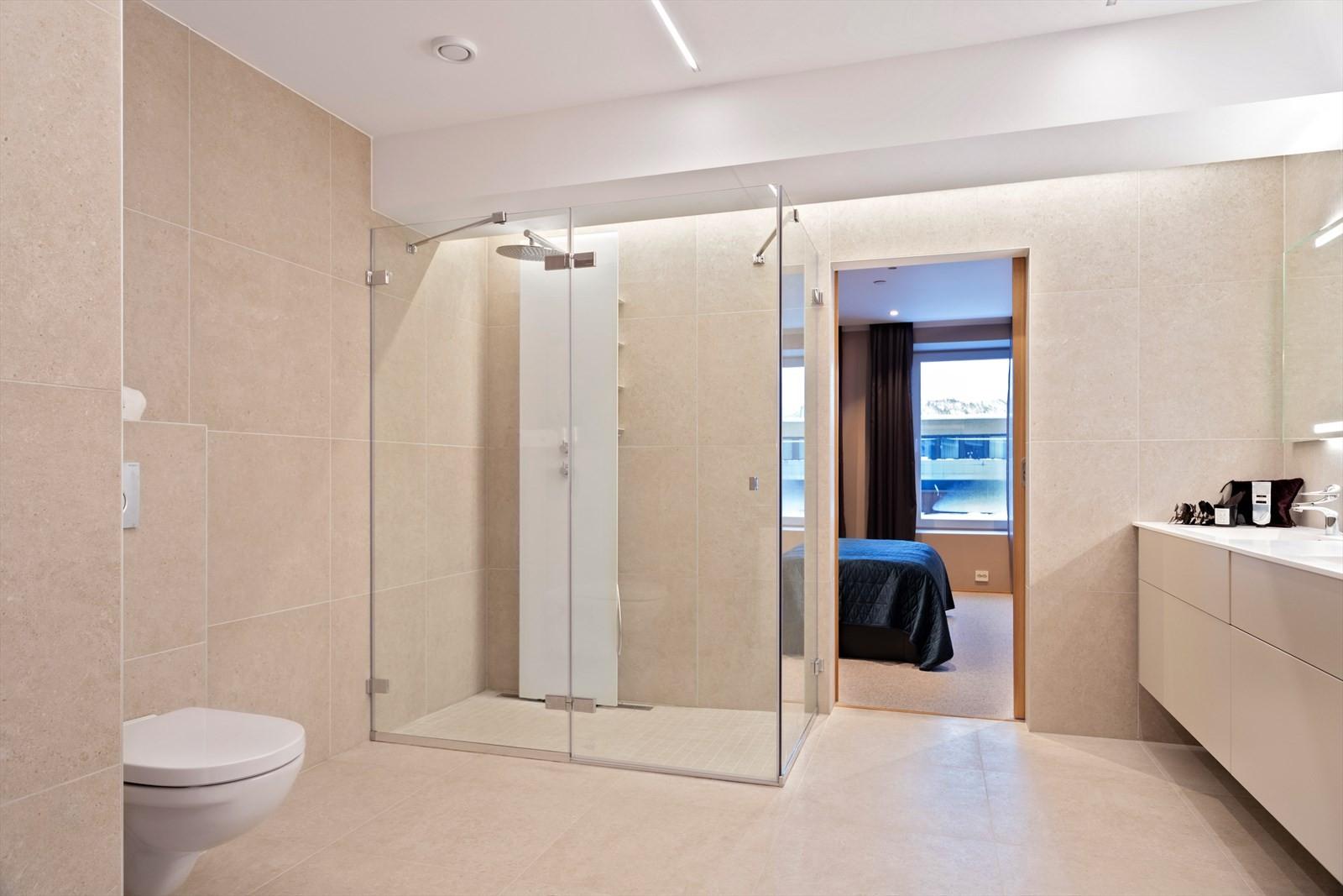 Badet er virkelig lekkert med eksklusive fliser, stor dusj, vegghengt klosett, innholdsrik innredning og med lekker belysning
