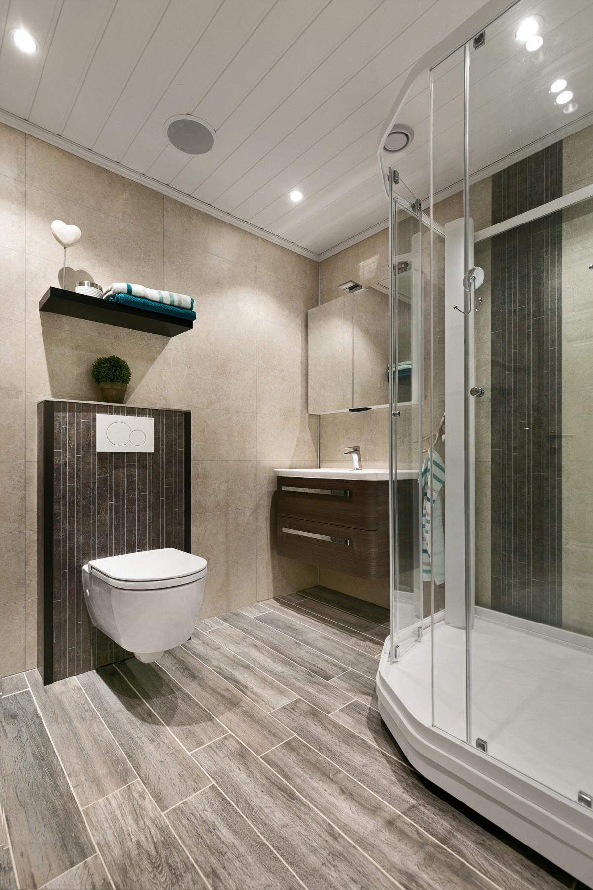 Komplett fliselagt baderom med spotter i tak, vegghengt toalett, baderomsinnredning og dusjkabinett