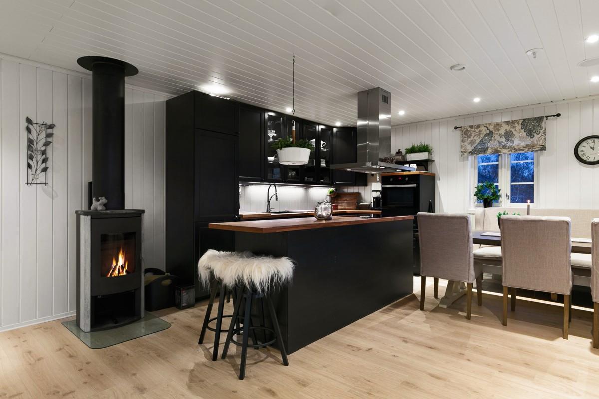 Stilfull og moderne kjøkkeninnredning. Praktisk vedfyring som sørger for god varme.