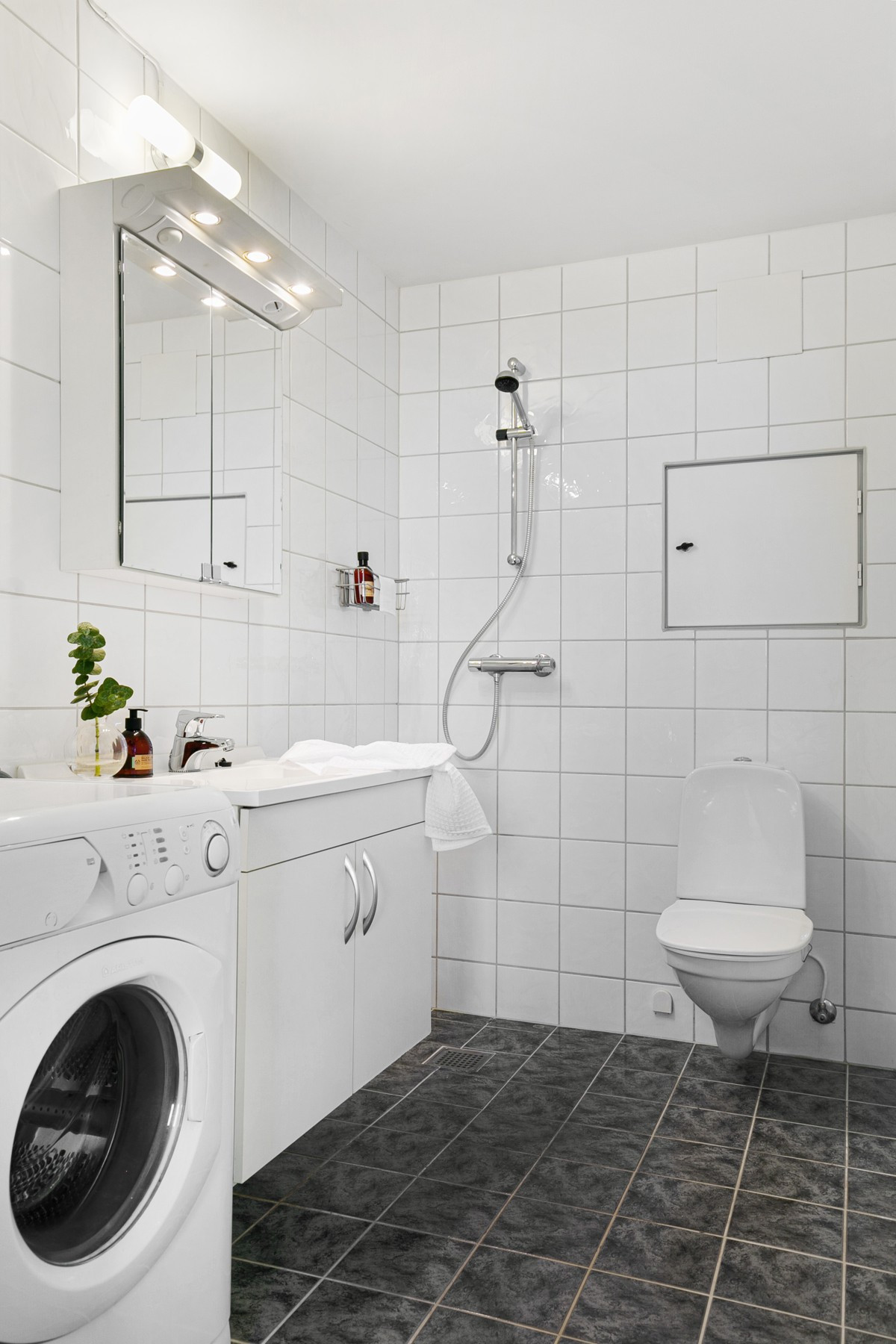 Komplett fliselagt baderom med dusjhjørne, wc og servant