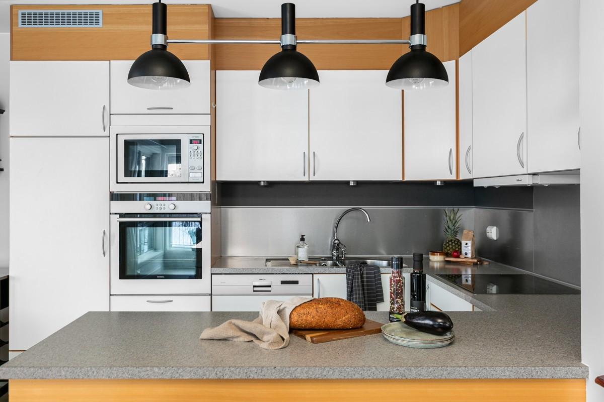Kjøkken er med hvite slette fronter, integrerte hvitevarer og laminat benkeplate