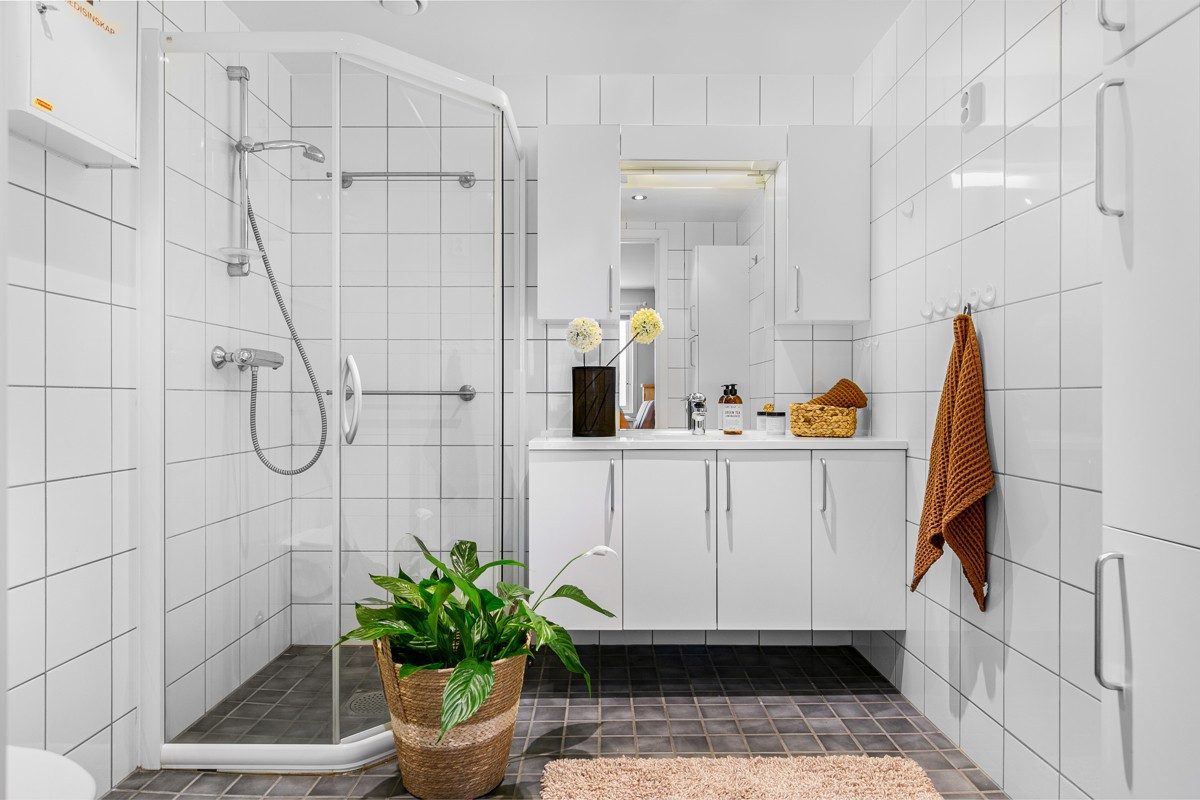 Fliselagt baderom med dusjhjørne, servant med oppbevaring og wc