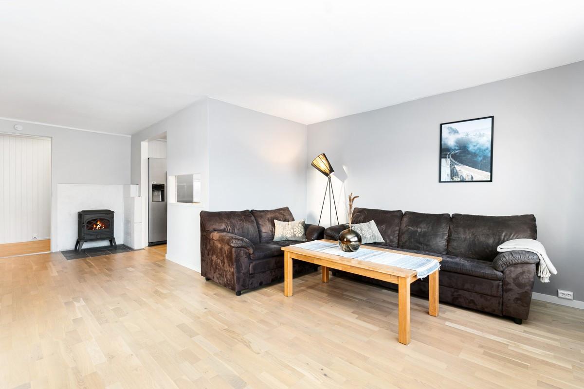Romslig stue med parkett på gulv, vedovn og lyse flater