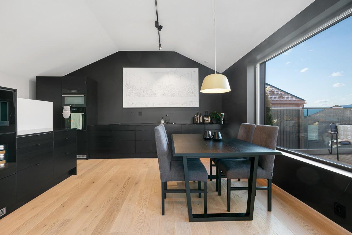 Kjøkken er moderne med sort innredning, rom for spisestue og store vindusflater