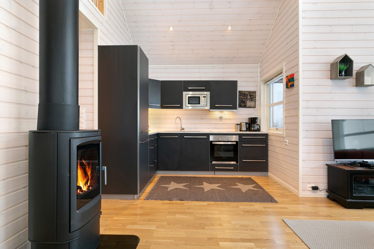 Kjøkken med glatte grå fronter og integrert koketopp, stekeovn, mikro oppvaskmaskin og kjøl / frys.