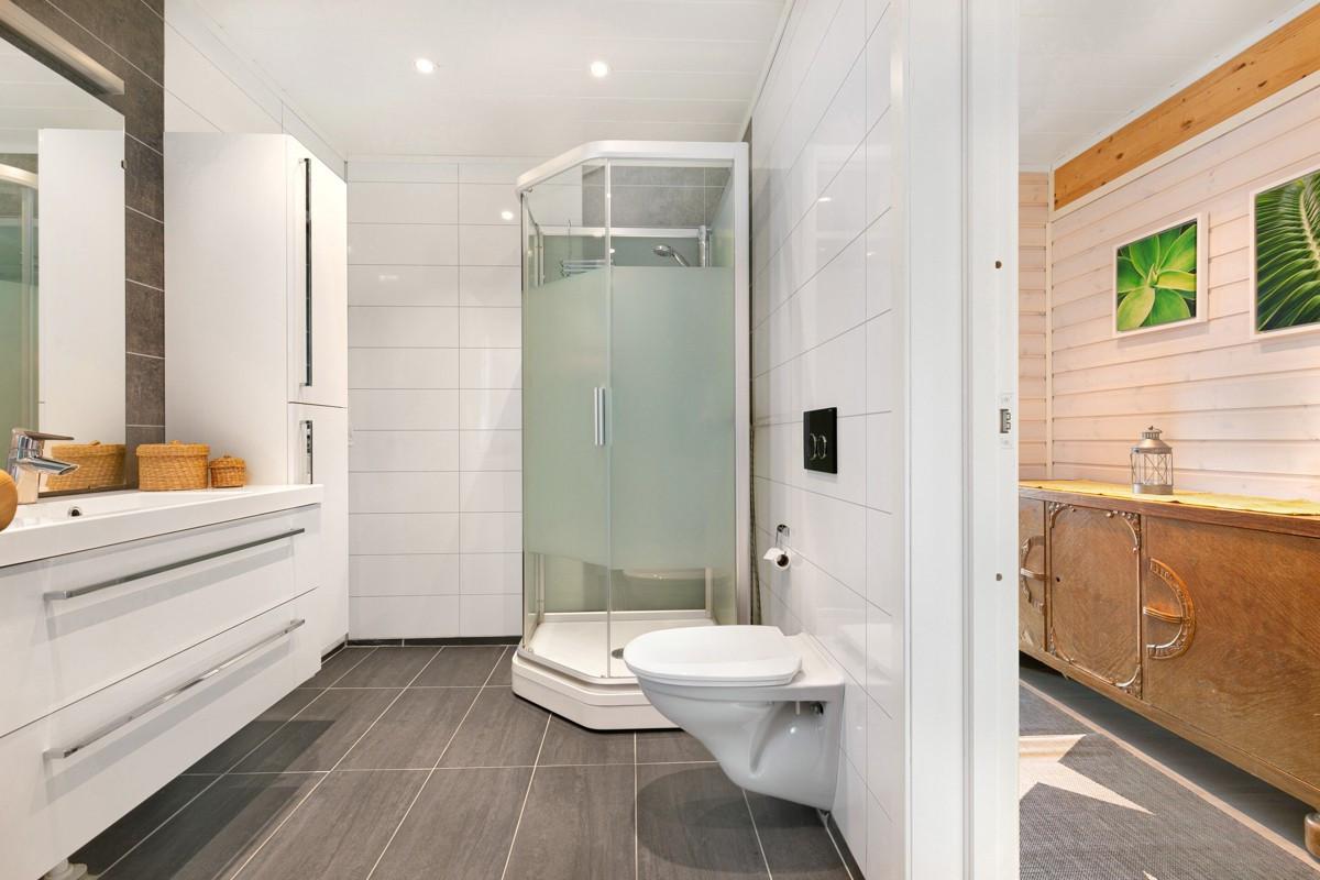 Badet har stor dusjnisje, vegghengt servant og spotter i tak som gir behagelig belysning