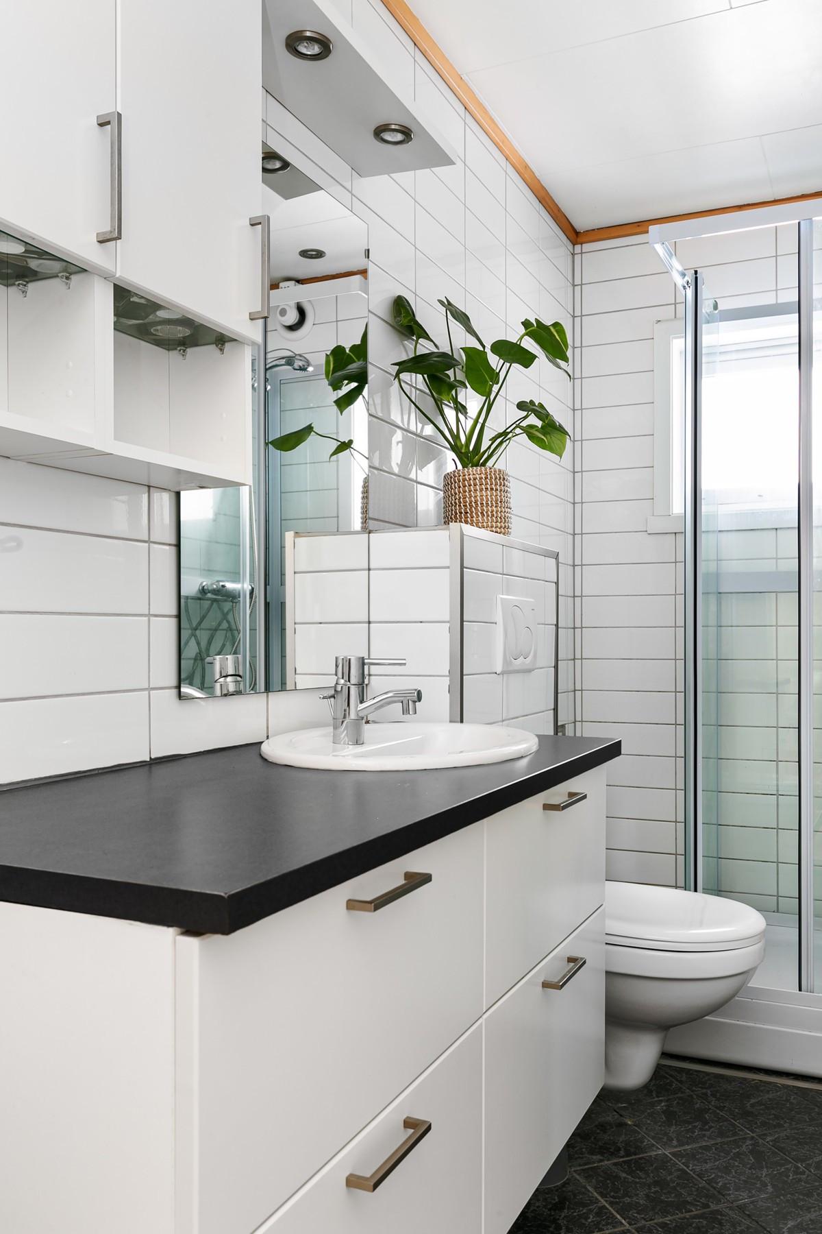 Komplett fliselagt baderom med dusjkabinett, servant og wc