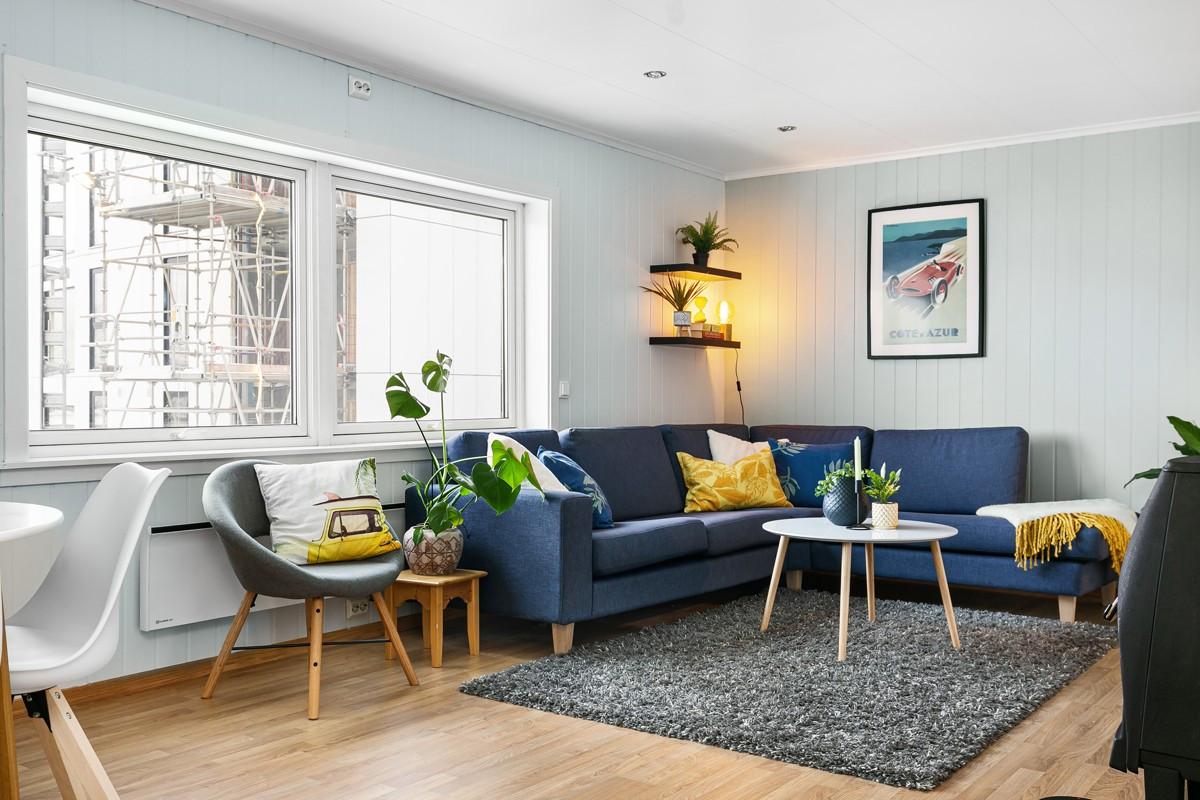 Innbydende og romslig stue med spotter i tak og lyse flater