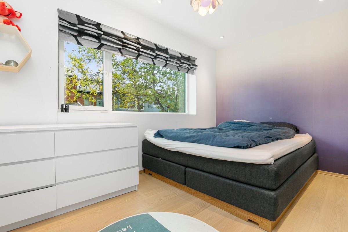 Soverom med fint fargevalg på vegger og god plass til garderobeskap