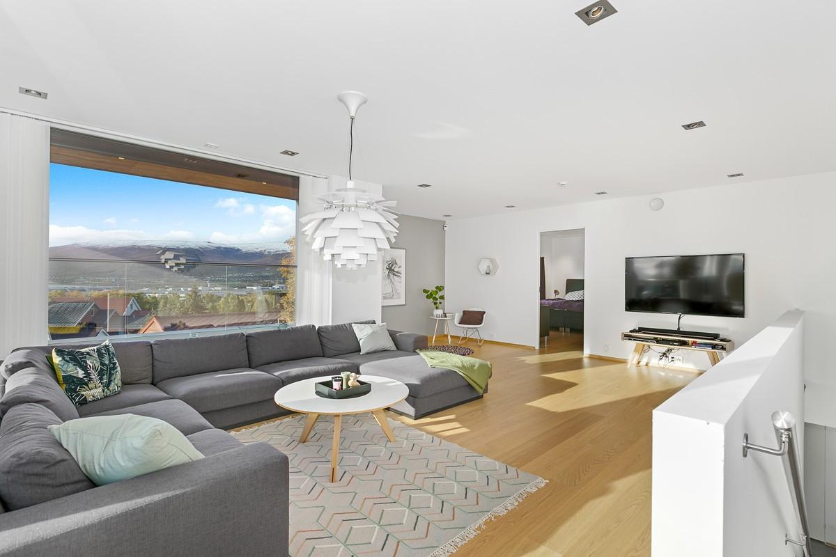 Stue med parkett på gulv og god plass til møblering