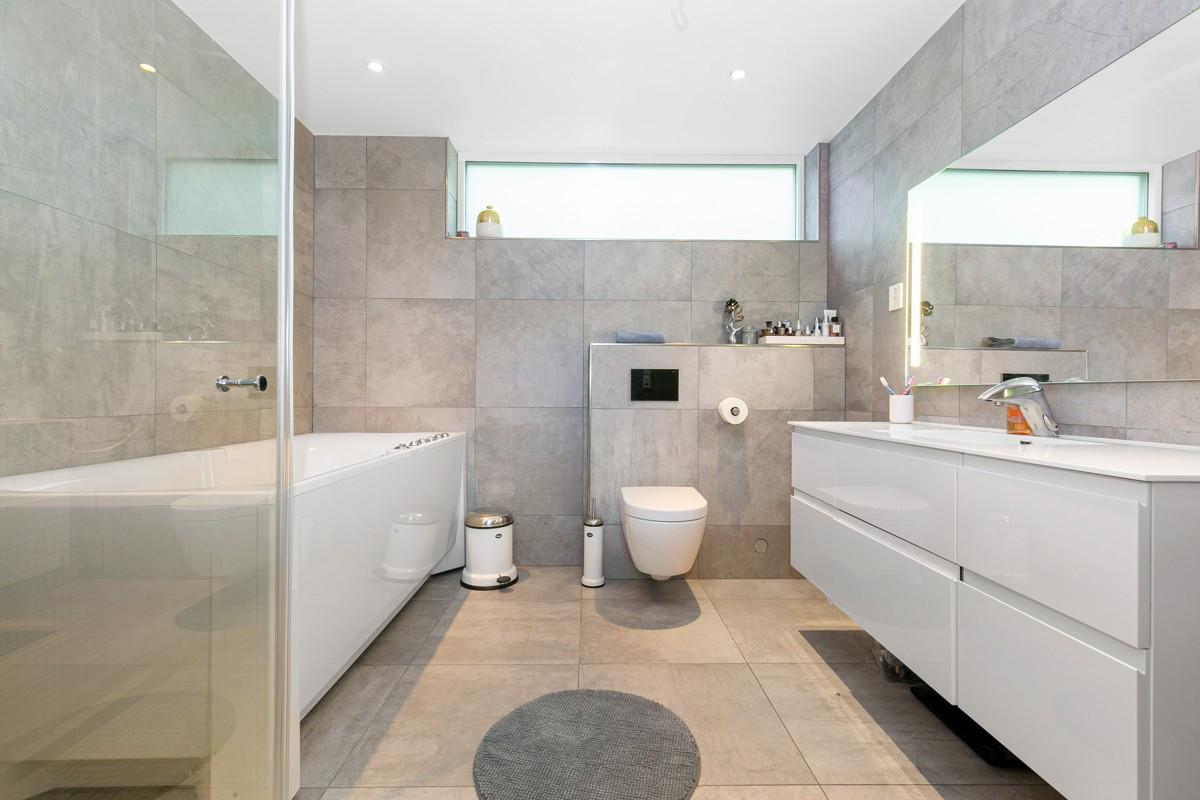 Badet er moderne innredet med vegghengt wc med elektrisk spyling og boblebadekar
