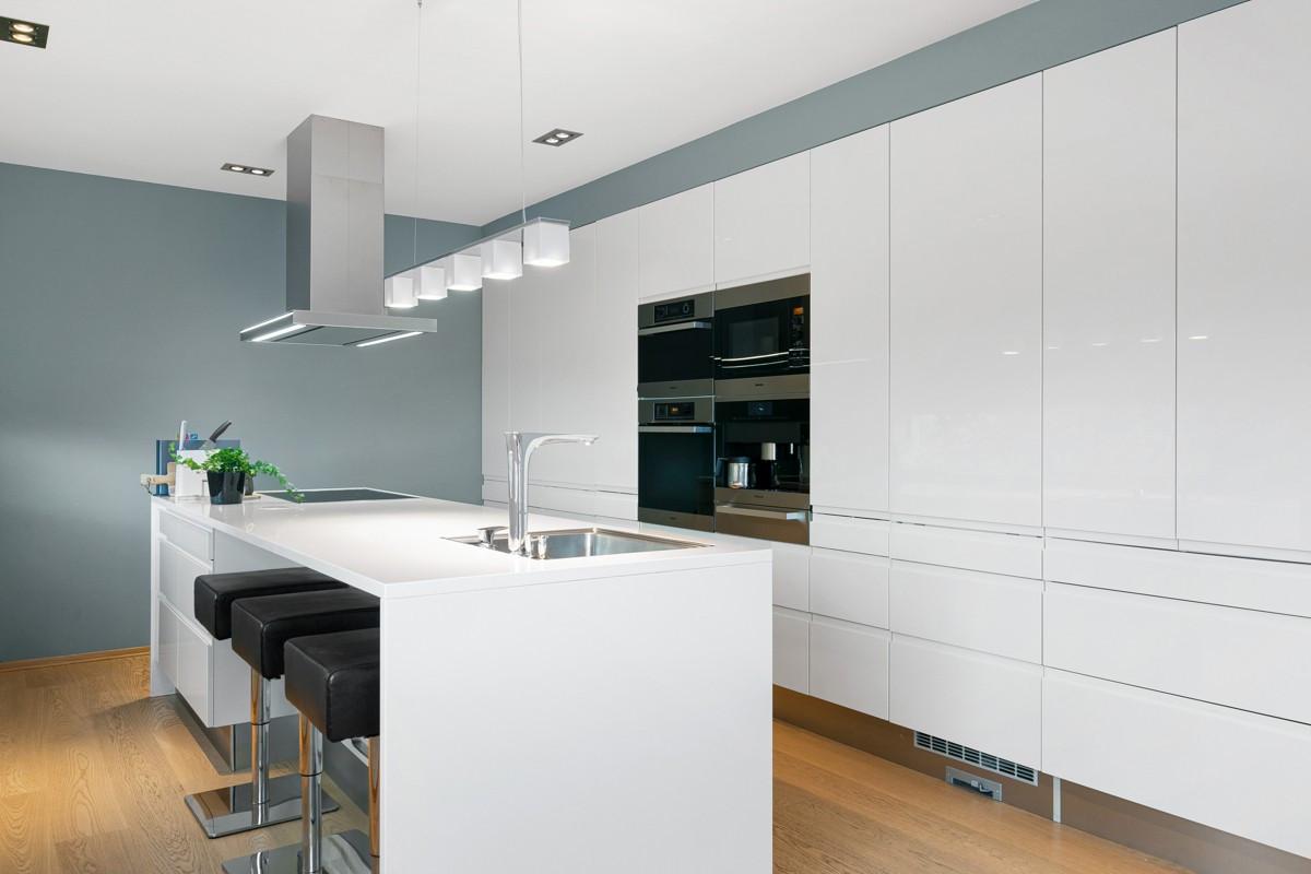 Moderne og påkostet kjøkkeninnredning med takhøye skap, integrerte hvitevarer og praktisk kjøkkenøy