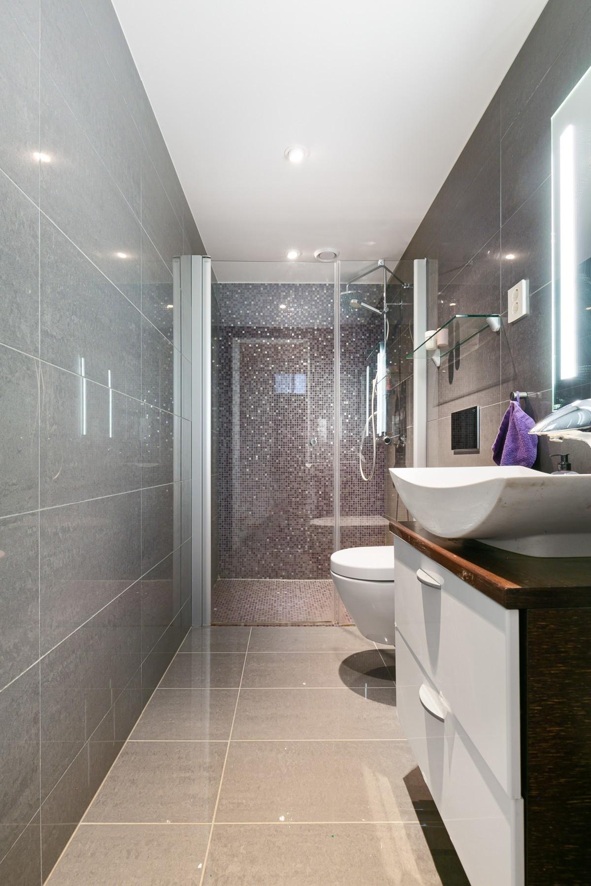 Bad i underetasje er komplett flislagt og moderne innredet med vegghengt wc og dusjnisje