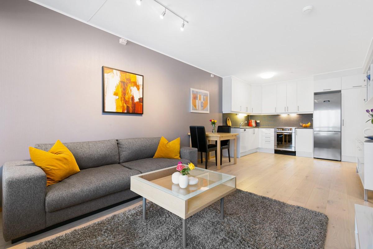 Stuen er med ny parkett på gulv, lyse flater og store vinduer ut mot sørvest