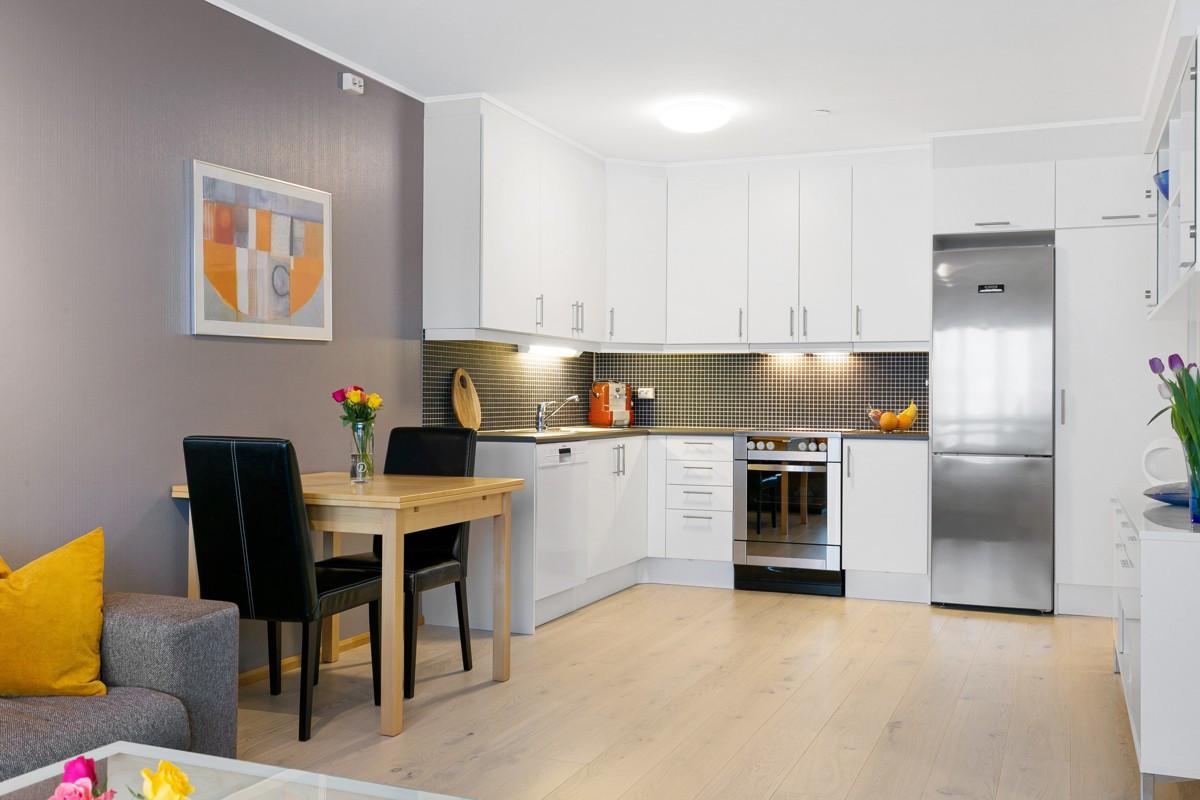 Kjøkken med takhøye skap og rom for kjøkkenbord