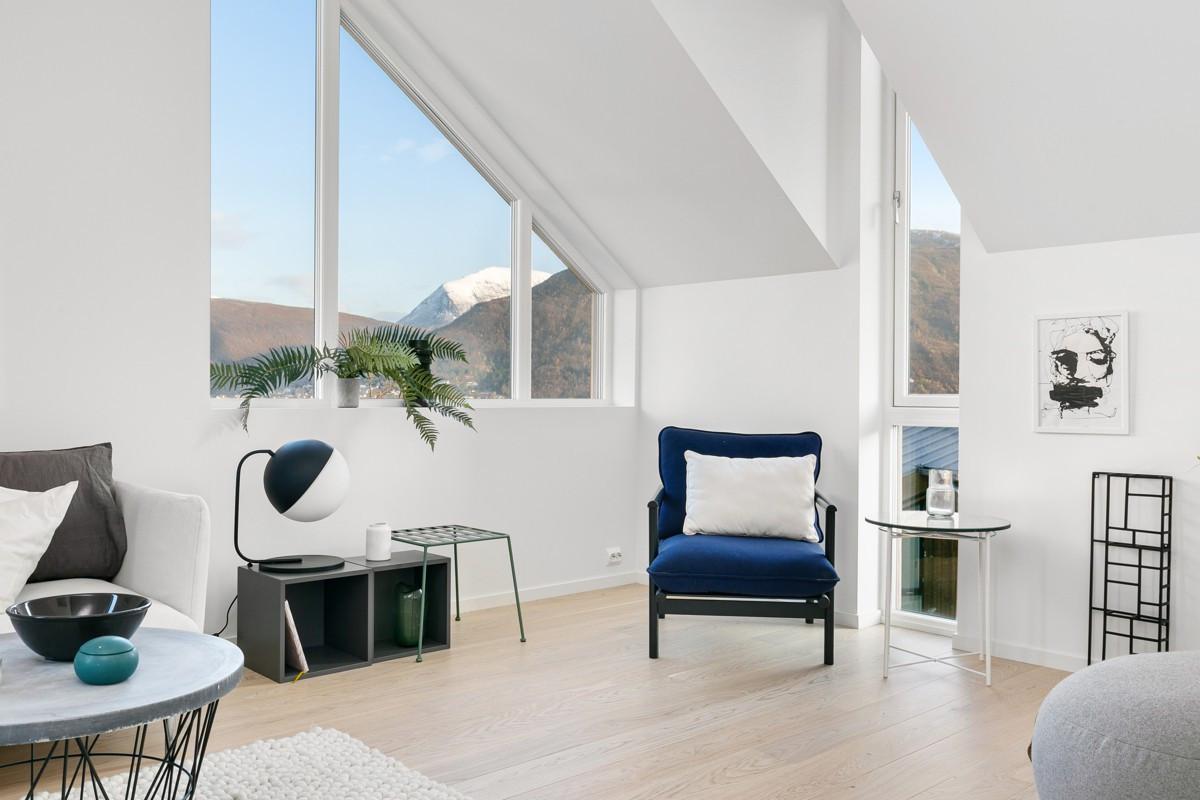 Kombinasjonen av mønehøyde på 3,4 m og store vindusflater gir rommet en romslig og