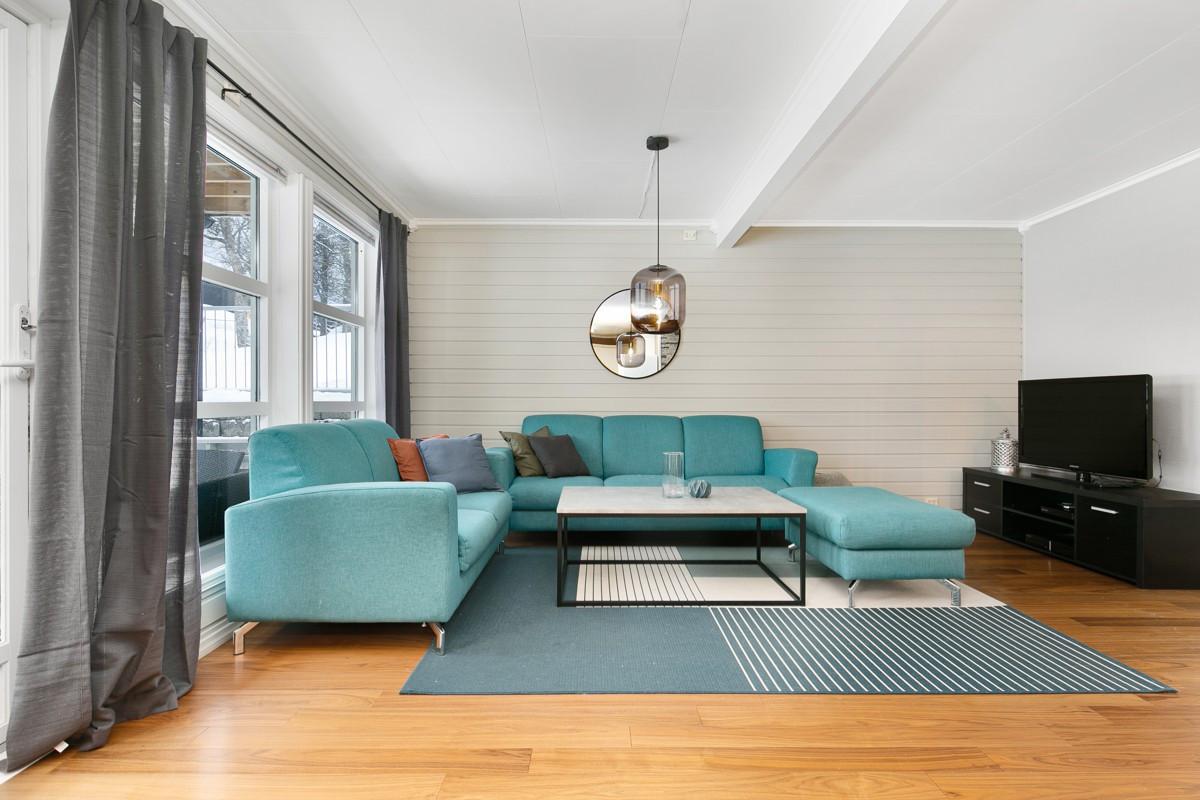 Stuen er romslig med store vindusflater som gir godt med lysinnslipp, lyse flater og laminat på gulv