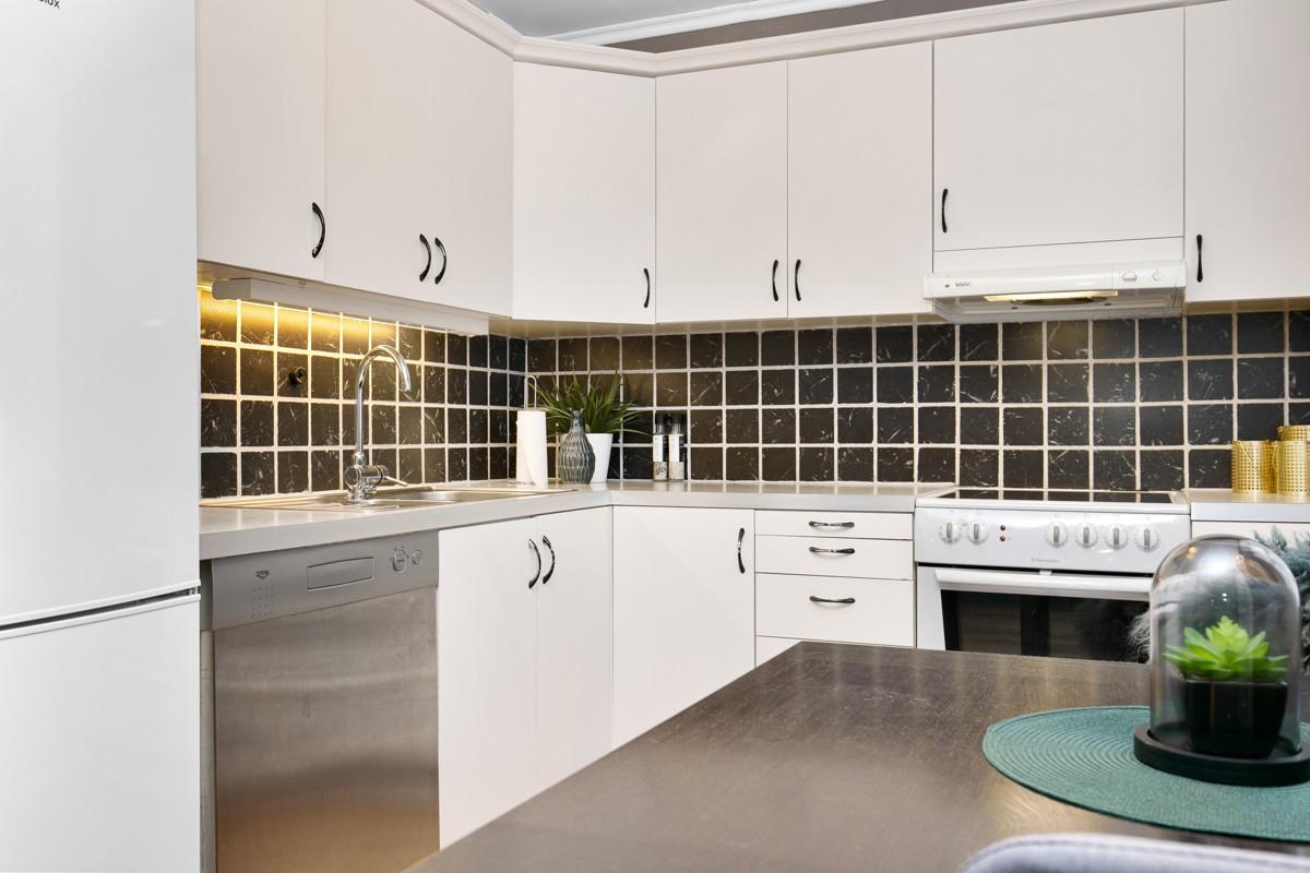 Kjøkkeninnredning med over- og underskap, fliser over benk og rikelig med skapplass