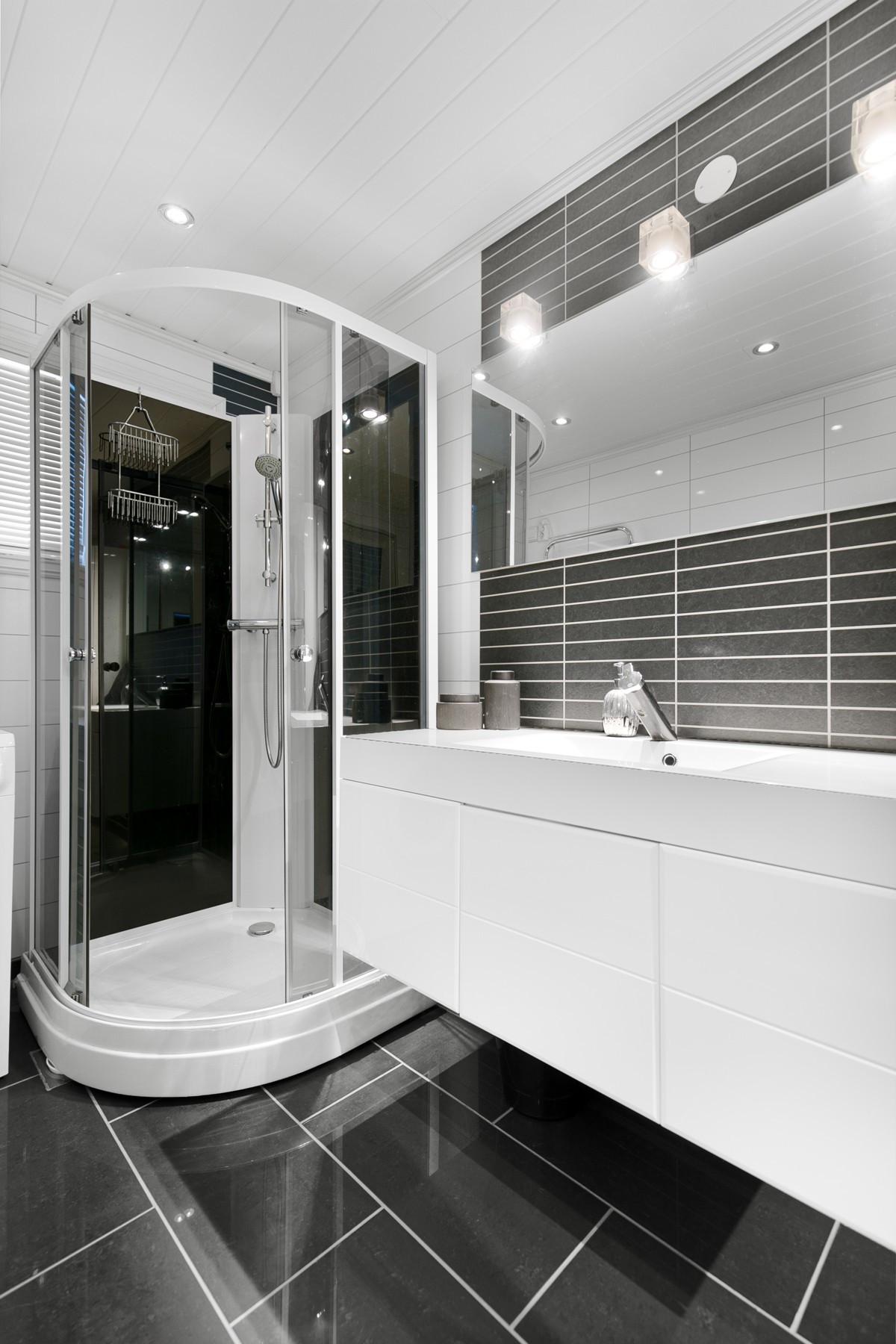 Moderne baderom med fliser og varme i gulv, dusjkabinett og oppbevaring i skuffer/høyskap