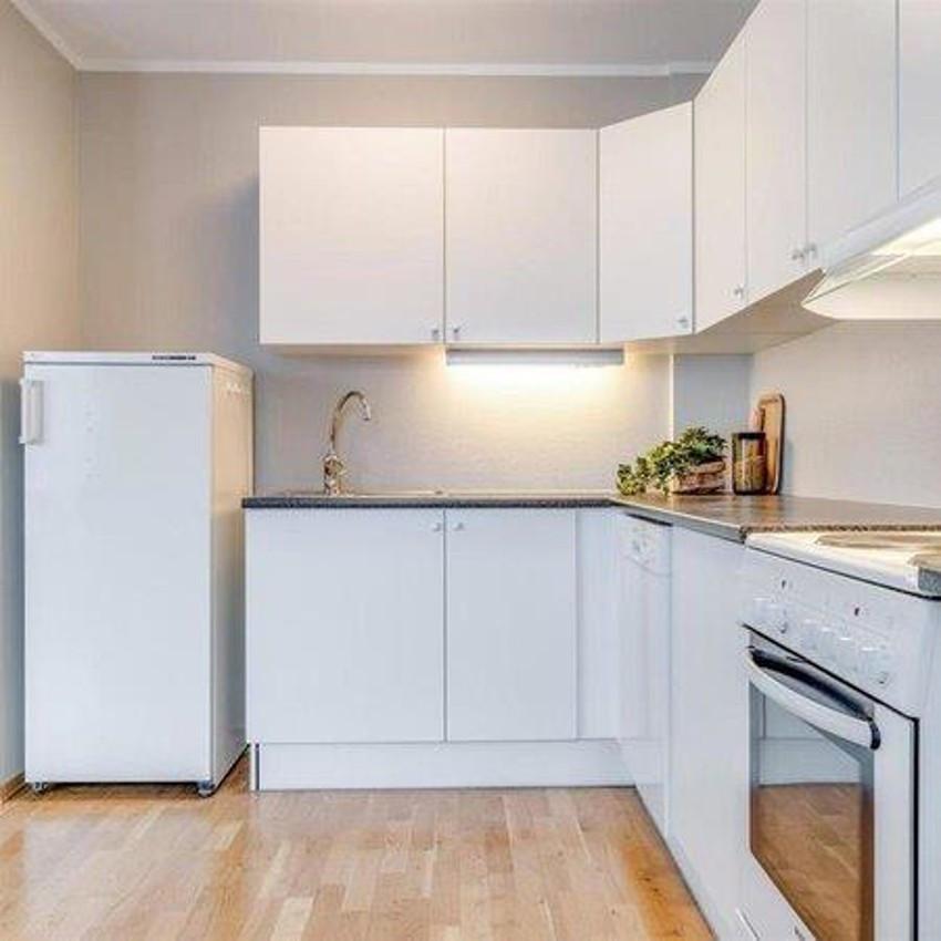 Kjøkkeninnredning med hvite glatte froner, samt gode oppbevaringsmuligheter i over- og underskap