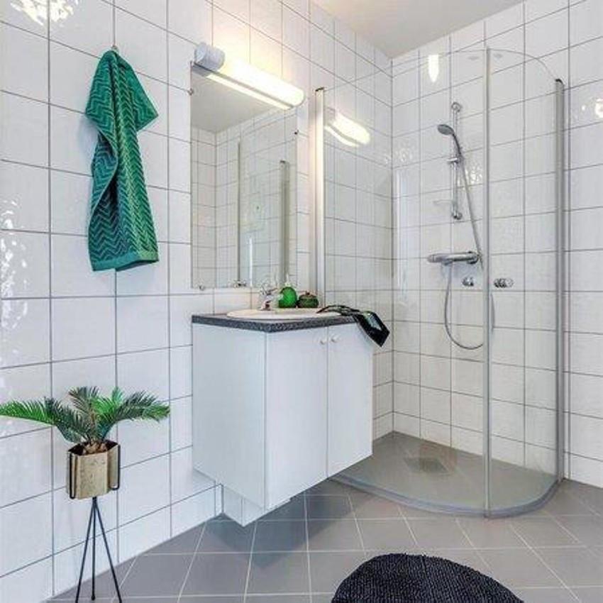 Fliselagt baderom med dusjhjørne, toalett og baderomsinnredning