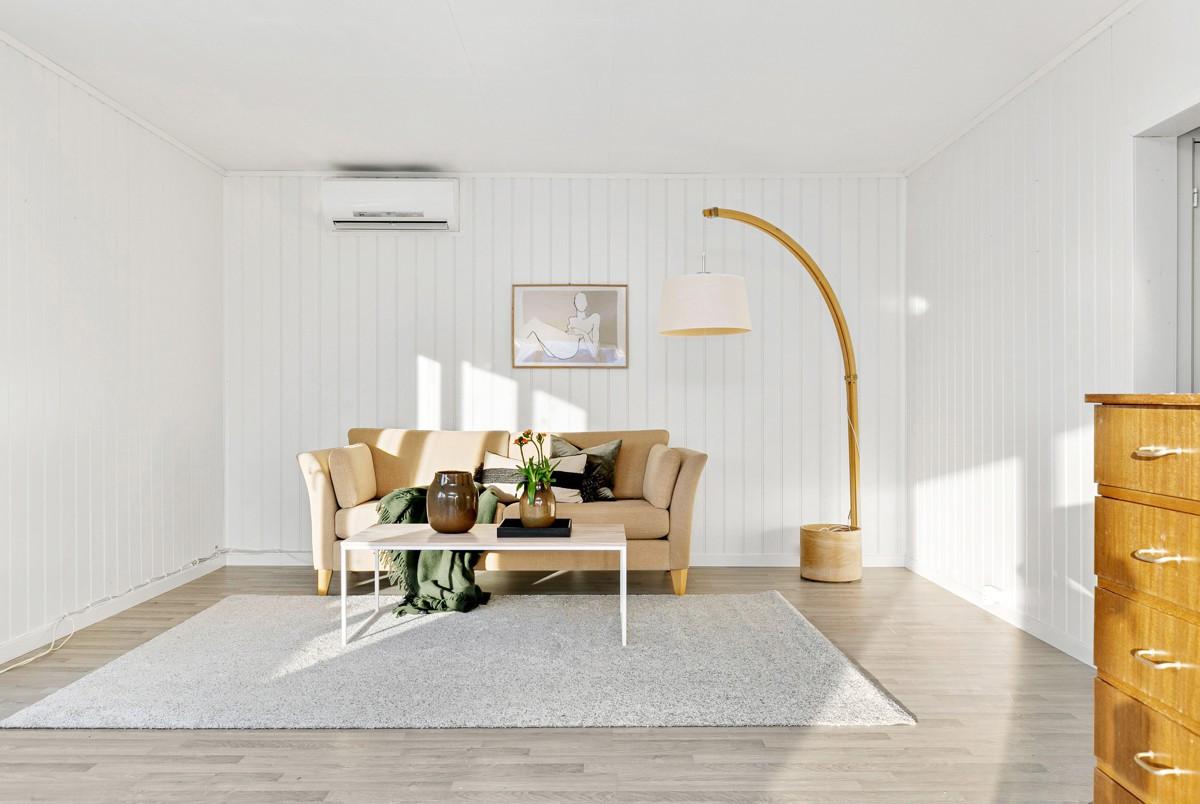 Stor og romslig stue med gode møbleringsmuligheter. Det er montert varmepumpe på vegg
