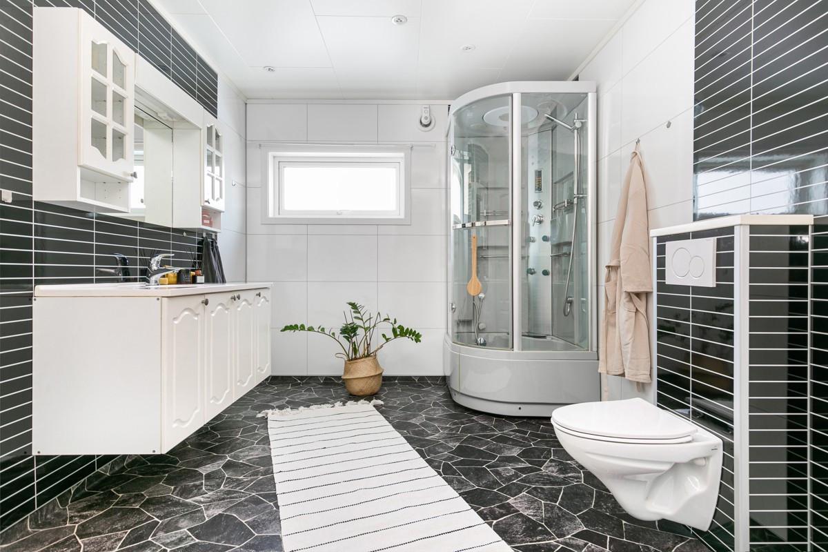 Stort og romslig baderom med vegghengt toalett og dusjkabinett
