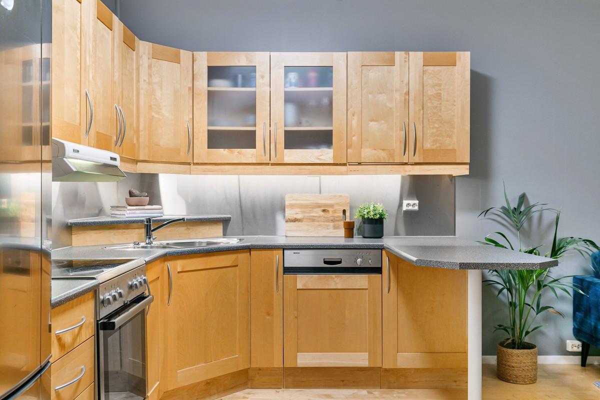 Kjøkken med profilerte fronter i bjørk og barløsning